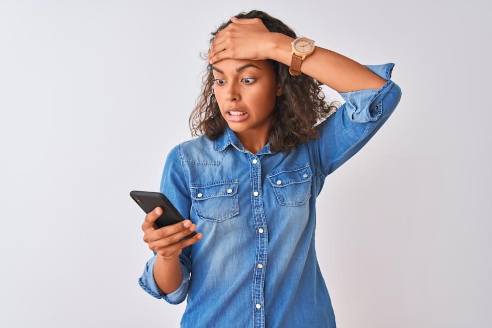 Young brazilian woman using smartphone standing over isolated white background stressed with hand on head, shocked with shame and surprise face, angry and frustrated. Fear and upset for mistake.