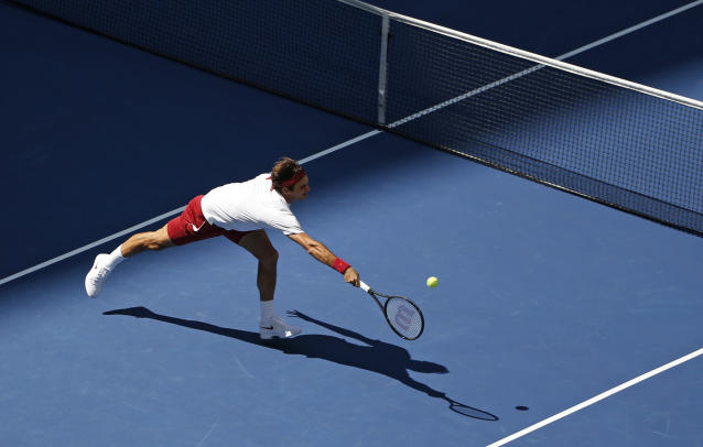 Roger Federer, of Switzerland, returns a shot to Nick Kyrgios, of Australia, during the third round of the U.S. Open tennis tournament, Saturday, Sept. 1, 2018, in New York. (AP Photo/Jason DeCrow)