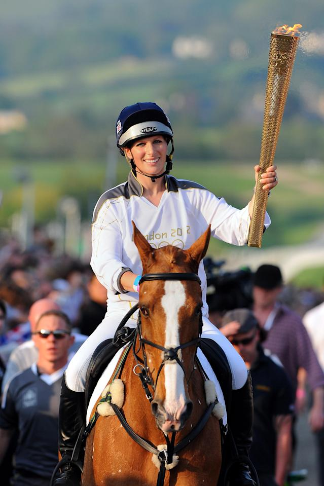 This photograph made available by LOCOG shows Britain's Queens Elizabeth's grand-daughter Zara Phillips carrying the Olympic Flame at the end of day 5 of the torch relay at Cheltenham Racecourse in Cheltenham England, Wednesday May 23, 2012. The Olympic torch relay is on its fifth day as it traverses Britain ahead of the July 27 opening of the London Games. Phillips has represented Britain in the 3-day-event. (AP Photo/Joe Giddens/LOCOG)