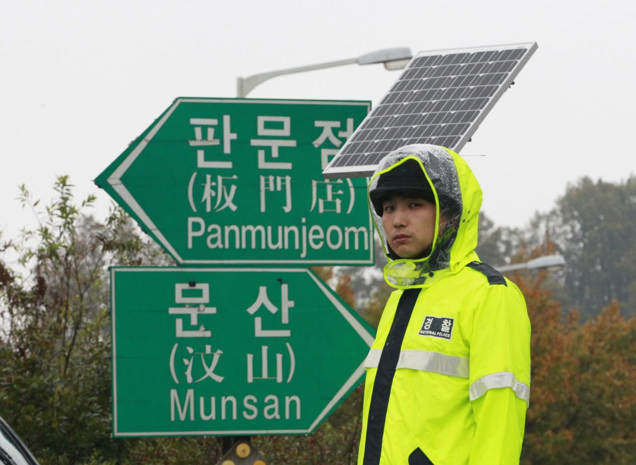 A police officer stands guard to block North Korean defector's planned rally on a road in Paju near demilitarized zone, South Korea, Monday, Oct. 22, 2012. South Korea has banned activists from launching propaganda leaflets to North Korea after North Korea threatened to attack.(AP Photo/Ahn Young-joon)