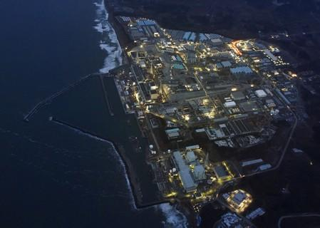 FILE PHOTO: Tokyo Electric Power Co.'s (TEPCO) tsunami-crippled Fukushima Daiichi nuclear power plant is illuminated for decommissioning operation in the dusk in Okuma town, Fukushima prefecture, Japan, in this aerial view photo taken by Kyodo