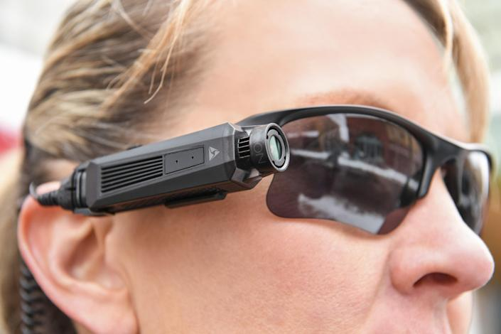 A person wearing the Axon Flex 2 camera attached to their sunglasses.