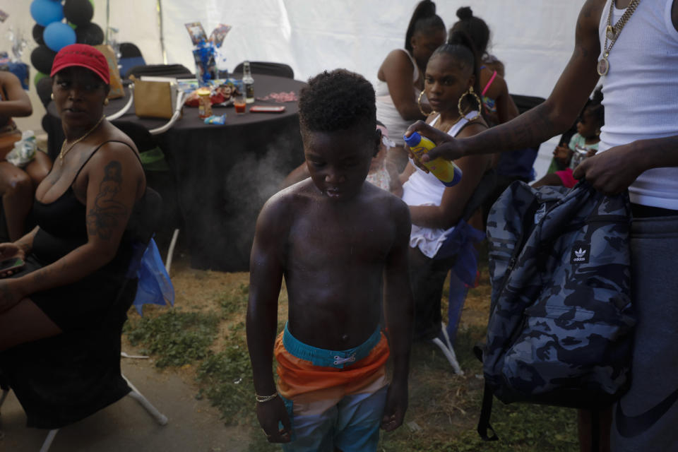 Emmett Palmer, right sprays sunscreen on Iron Grim, 6, as tenants gather for a birthday party at the Nickerson Gardens housing project in the Watts neighborhood of Los Angeles, Wednesday, June 10, 2020. (AP Photo/Jae C. Hong)