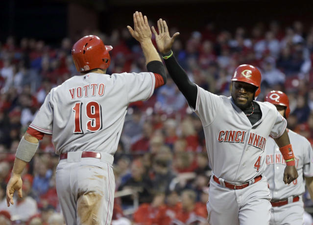 Cincinnati Reds' Brandon Phillips, right, and Joey Votto celebrate after scoring on a two-run triple by Jay Bruce during the first inning of a baseball game against the St. Louis Cardinals on Tuesday, April 8, 2014, in St. Louis. (AP Photo/Jeff Roberson)