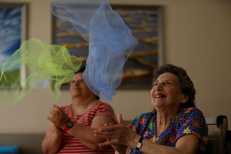 Elderly residents clap before catching coloured scarves during an activity session run by ACTive Age Malta at Hilltop Gardens retirement village in Naxxar, Malta, July 3, 2017. REUTERS/Darrin Zammit Lupi