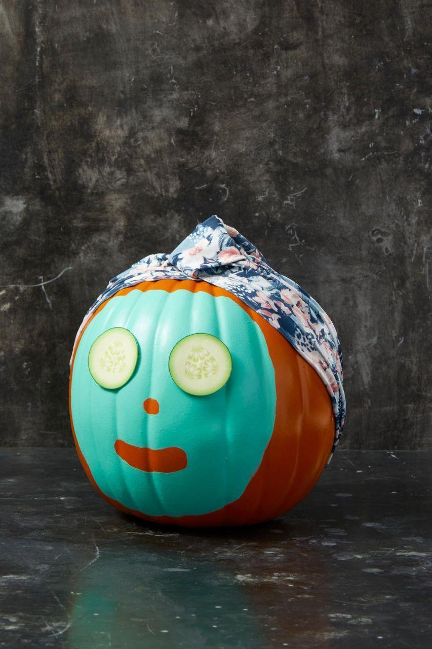"""<p>Who says pumpkins don't deserve little self-care?</p><p><strong>Make the Pumpkin: </strong>Paint a """"face mask"""" on a real or faux pumpkin, leaving spaces for the nose and mouth. Let it dry completely. Stretch a decorative shower cap onto the pumpkin's """"head"""" and pin in place with straight pins. To make the cucumber eyes, just print images of cucumbers from a picture online and glue them on. </p>"""