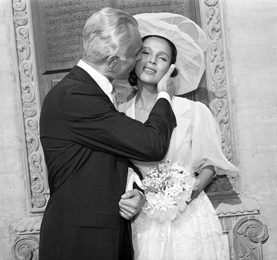 <p>Dorothy Dandridge receives a kiss from her husband outside of Los Angeles's St. Sophia Orthodox Cathedral following their ceremony. For her wedding to the restaurant owner, Dandridge wore a chiffon gown with bishop sleeves and a sheer wide-brimmed hat. </p>