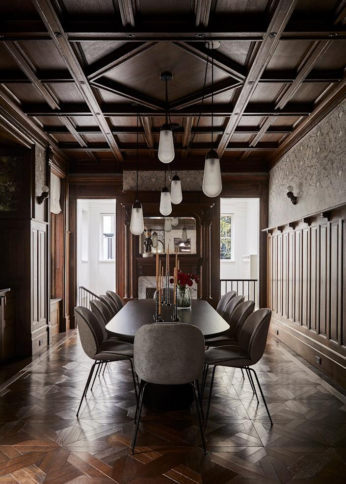 "<div class=""caption""> The dining room, which had been turned into a kitchen when the residence became a multifamily unit, maintained its original coffered ceilings and some wall panels. Architect Jeffery Povero recreated the rest of the panels in the room. To add some ""gothic glamour"" to the space, designer Gillian Dubin chose a <a href=""https://www.timorousbeasties.com"" rel=""nofollow noopener"" target=""_blank"" data-ylk=""slk:Timorous Beasties"" class=""link rapid-noclick-resp"">Timorous Beasties</a> wallpaper printed with clusters of dark moths. The black-stained table and upholstered chairs are from <a href=""https://shop.gubi.com"" rel=""nofollow noopener"" target=""_blank"" data-ylk=""slk:Gubi"" class=""link rapid-noclick-resp"">Gubi</a>. </div>"