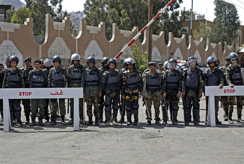 Yemeni soldiers stand guard as protestors, unseen, demand the release of their detained relatives in Guantanamo Bay prison, during a demonstration in front of US embassy in Sanaa, Yemen, Monday, April 1, 2013. (AP Photo/Hani Mohammed)