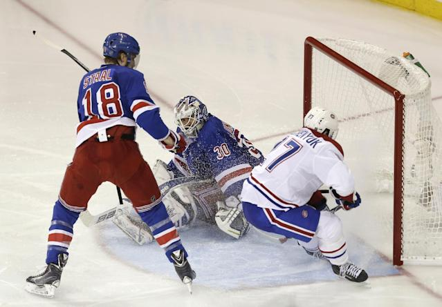 Montreal Canadiens' Alex Galchenyuk, right, scores past New York Rangers goalie Henrik Lundqvist and Rangers' Marc Staal, left, during overtime of Game 3 of the NHL hockey Stanley Cup playoffs Eastern Conference finals, Thursday, May 22, 2014, in New York. The Canadiens won 3-2. (AP Photo/Seth Wenig)