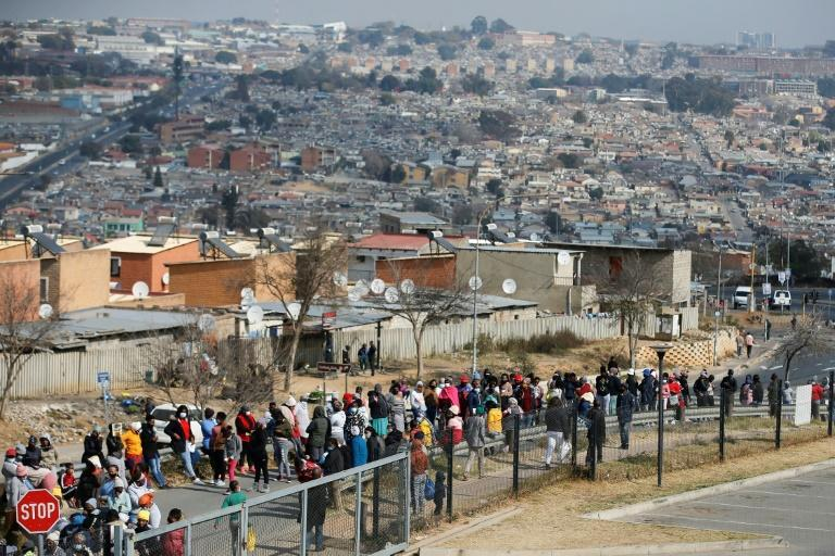 People queue outside the Alex Mall in Alexandra township near Johannesburg