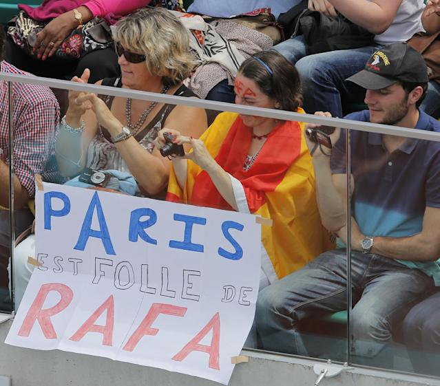 """Tennis fans, one draped in the Spanish flag, sit next to a sign reading """"Paris is crazy about Rafa"""", referring to Spain's Rafael Nadal who played his fourth round match of the French Open tennis tournament against Serbia's Dusan Lajovic at the Roland Garros stadium, in Paris, France, Monday, June 2, 2014. (AP Photo/Michel Spingler)"""