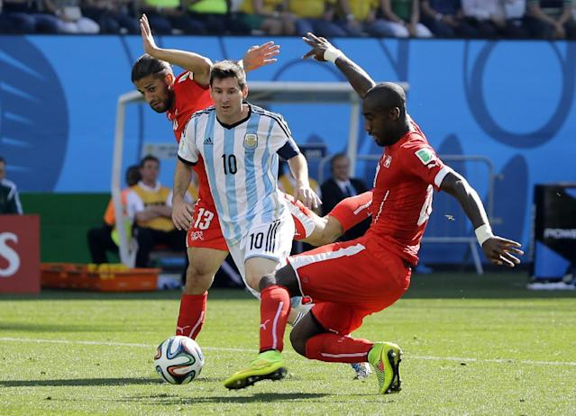 Switzerland's Ricardo Rodriguez, left, and Johan Djourou challenge Argentina's Lionel Messi during the World Cup round of 16 soccer match between Argentina and Switzerland at the Itaquerao Stadium in Sao Paulo, Brazil, Tuesday, July 1, 2014. (AP Photo/Sergei Grits)