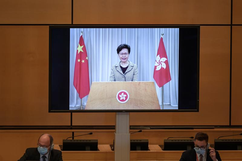 """Hong Kong's chief executive Carrie Lam is seen on a giant screen remotely addressing the opening of the UN Human Rights Council's 44th session on June 30, 2020 in Geneva. - Hong Kong's chief executive defended China's sweeping national security law for the city before the United Nations, urging the international community to """"respect our country's right to safeguard national security."""" (Photo by Fabrice COFFRINI / AFP) (Photo by FABRICE COFFRINI/AFP via Getty Images)"""