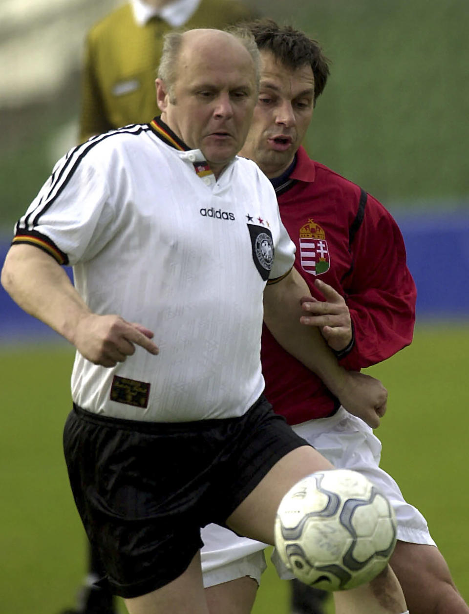 FILE - In this Tuesday April 24, 2001 file photo Hungarian Prime Minister Viktor Orban, right, and German lawmaker Heinz Schmitt fight for the ball during a friendly international soccer match between Hungarian Parliament and German Bundestag in Budapest. Populist Prime Minister Viktor Orban has long used soccer to advance his right-wing politics, and now widespread international criticism of a new Hungarian law that is seen as targeting the LGBT community has turned this month's Euro 2020 tournament into a major stage for his challenge to Europe's liberal values. (AP Photo/MTI, Szilard Koszticsak, File)