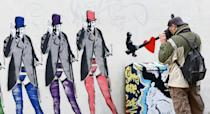 A man photographs a mural of wartime leader Sir Winston Churchill wearing stockings and suspenders and giving the 'V' sign by illusive local artist who goes by the name Horace, on the side of the Sandpiper guest house in Brighton.