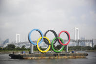 """FILE - In this Aug. 6, 2020, file photo, the Olympic rings for the Olympic and Paralympic Games Tokyo 2020 pass by on a barge by tugboats off the Odaiba Marine Park in Tokyo. Tokyo Olympic officials said Thursday, Dec. 24, they have reached a """"basic agreement"""" with all 68 domestic sponsors to extend their contracts into next year to support the postponed Games. (AP Photo/Hiro Komae, File)"""