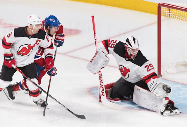 Montreal Canadiens' Brendan Gallagher (11) moves in against New Jersey Devils goaltender Mackenzie Blackwood as Devils' Andy Greene (6) defends during second-period NHL hockey game action in Montreal, Thursday, Nov. 28, 2019. (Graham Hughes/The Canadian Press via AP)