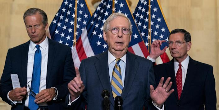 Senate Minority Leader Mitch McConnell stands between Senate Minority Whip Sen. John Thune, left, and Sen. John Barrasso with his hands raised, speaking with reporters on Capitol Hill.