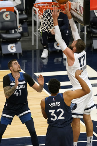 Memphis Grizzlies' Jonas Valanciunas (17) lays up a shot as Minnesota Timberwolves' Juancho Hernangomez (41) and Karl-Anthony Towns watch in the first half of an NBA basketball game, Wednesday, Jan. 13, 2021, in Minneapolis. (AP Photo/Jim Mone)