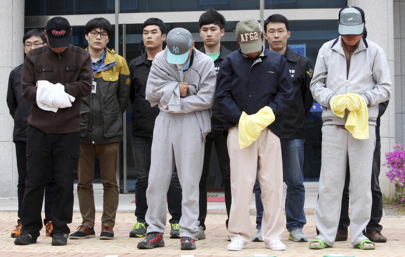 Crew members of sunken ferry Sewol prepare to leave a court which issued their arrest warrant, in Mokpo, South Korea, Saturday, April 26, 2014. All 15 people involved in navigating the South Korean ferry that sank and left scores of people dead or missing are now in custody after authorities on Saturday detained four more crew members, a prosecutor said. (AP Photo/Yonhap) KOREA OUT