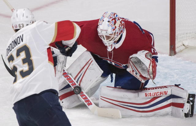 Montreal Canadiens goaltender Antti Niemi, right, makes a save against Florida Panthers right wing Evgenii Dadonov (63) during first-period NHL hockey game action in Montreal, Monday, March 19, 2018. (Graham Hughes/The Canadian Press via AP)