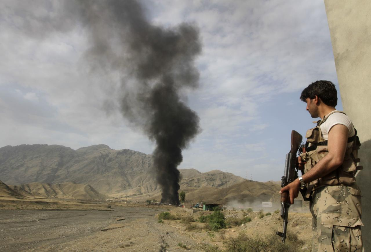 Afghan security forces keep watch as smoke rises from burning NATO supply trucks after, what police officials say, was an attack by militants in the Torkham area near the Pakistani-Afghan in Nangarhar Province June 19, 2014. According to officials on Thursday, at least 37 trucks belonging to NATO forces were destroyed after three suicide bombers targeted the NATO supply trucks, with two civilians wounded in the attack. REUTERS/Parwiz (AFGHANISTAN - Tags: CIVIL UNREST POLITICS)