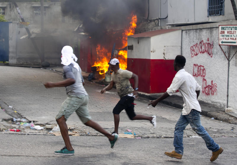 Demonstrators run past a torched structure after local neighborhood residents clashed with demonstrators during a protest to demand the resignation of Haiti's president Jovenel Moise on the 216th anniversary of Battle of Vertieres in Port-au-Prince, Haiti, Monday, Nov. 18, 2019. At least four people were shot and wounded during a small protest in Haiti's capital after a speech by embattled President Moise. A local journalist, a police officer and two protesters were rushed away with apparent bullet wounds. (AP Photo/Dieu Nalio Chery)