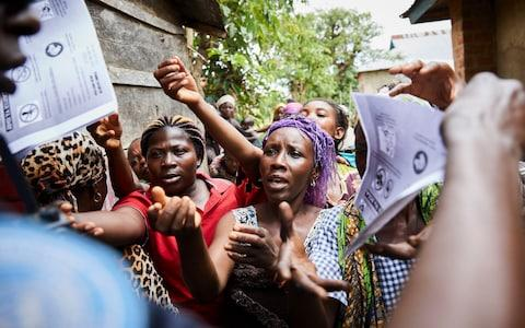 Villagers react as the United Nations Police forces conduct an Ebola awareness campaign - Credit: HUGH KINSELLA CUNNINGHAM/EPA-EFE/REX