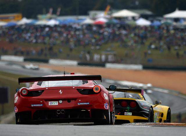 Matteo Malucelli, of Italy, drives the Risi Competizione Ferrari F458 as he follows Jan Magnussen (3), of Denmark, in the Chevrolet Corvette C6.R during the American Le Mans Series' Petit Le Mans auto race at Road Atlanta, Saturday, Oct. 19, 2013, in Braselton, Ga. (AP Photo/Rainier Ehrhardt)
