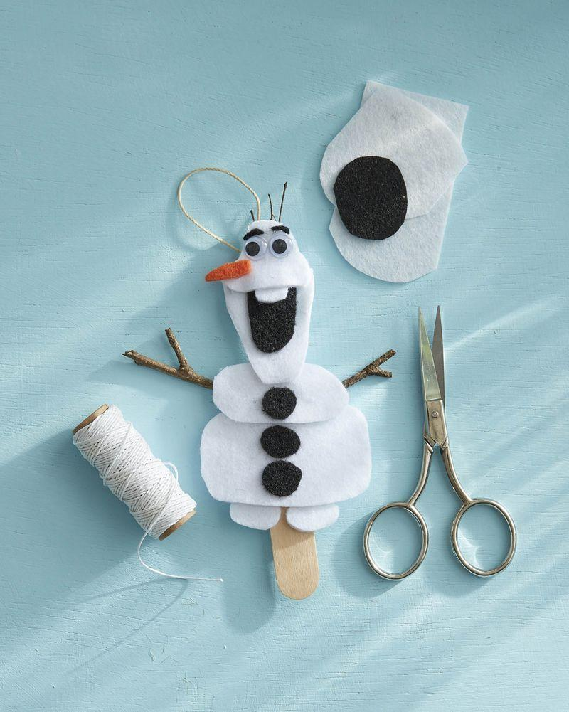 """<p>Kids love <em>Frozen,</em> and this ornament will surely get them dancing around the tree signing """"Let It Go"""" again and again (sorry parents!).</p><p><strong>To make:</strong> Cut body shapes from white felt; attach to a tongue depressor with hot glue. Cut buttons, mouth and eyebrows from black felt; attach to body with hot glue. Glue mini googly eyes below the eyebrows. Cut a carrot nose from orange felt; attach below the eyes with hot glue. Glue mini twig arms and a piece of twine for hanging to the tongue depressor.</p><p><a class=""""link rapid-noclick-resp"""" href=""""https://www.amazon.com/Pieces-Wiggle-Adhesive-Scrapbooking-Assorted/dp/B01GPVFZHK/ref=sr_1_4?tag=syn-yahoo-20&ascsubtag=%5Bartid%7C10050.g.1070%5Bsrc%7Cyahoo-us"""" rel=""""nofollow noopener"""" target=""""_blank"""" data-ylk=""""slk:SHOP GOOGLE EYES"""">SHOP GOOGLE EYES</a></p>"""