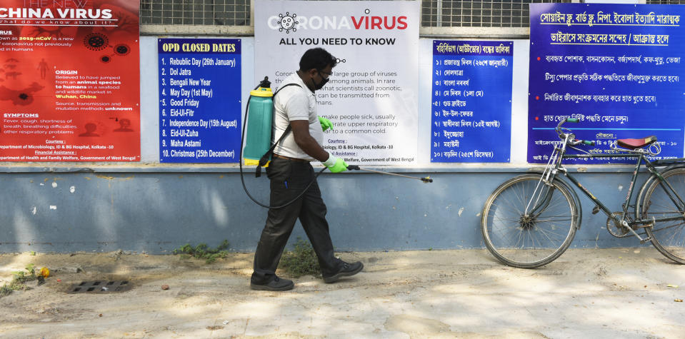 A man sprays while he passes by the posters for the prevention against Coronavirus in Kolkata, India, 13 March, 2020. India records first death due to Coronavirus in the India state of Karnataka. India has 81 confirmed cases of Coronavirus according to an Indian media report.  (Photo by Indranil Aditya/NurPhoto via Getty Images)