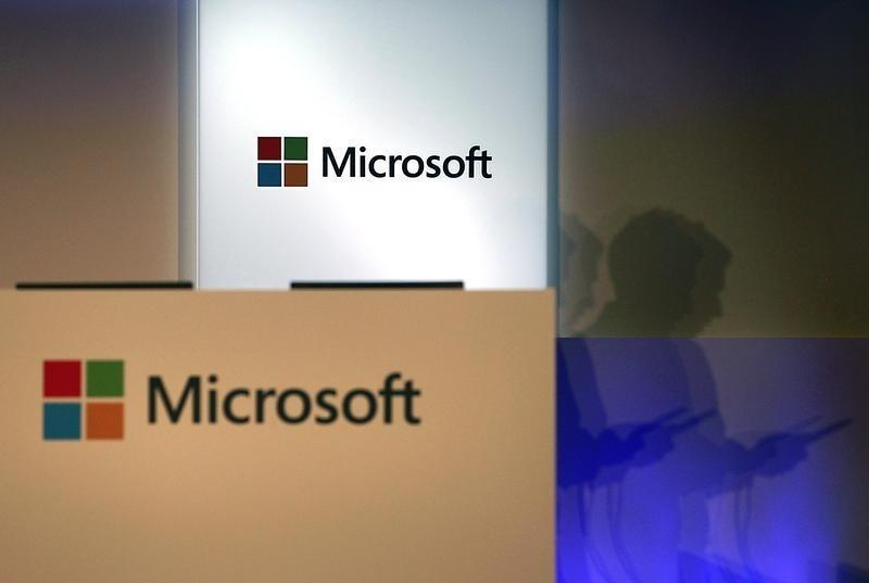 A shadow of a man using his mobile phone is cast near Microsoft logo at the 2014 Computex exhibition in Taipei