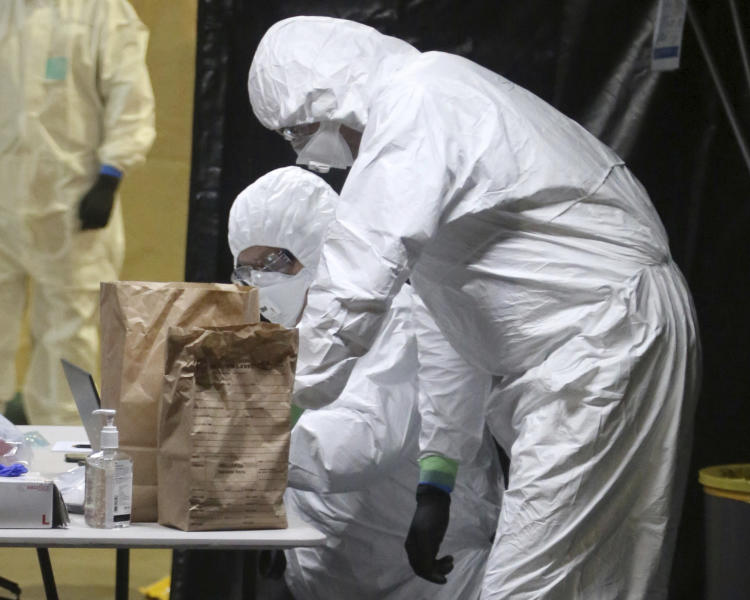 In this Wednesday, April 8, 2020, photo provided by the New South Wales Police, investigators in protective gear examine material from the Ruby Princess cruise ship at Wollongong, Australia. Police boarded the cruise ship to seize evidence and question crew members after the vessel was linked to hundreds of COVID-19 cases and more than a dozen deaths across Australia. (Nathan Patterson/NSW Police via AP)