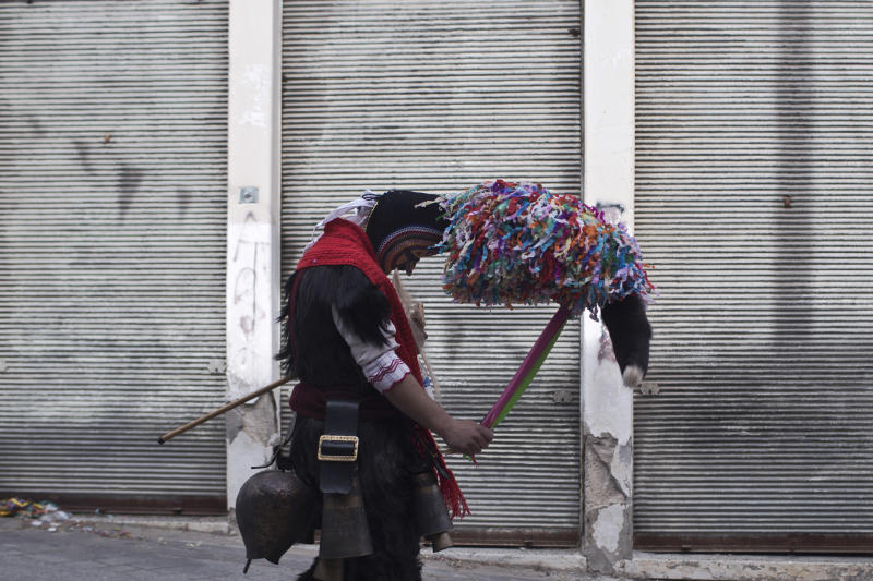 In this Monday March 11, 2019 photo, a man wearing a goat hide with bells around his waist and a mask that include a meter tall, ribbon-covered formation topped with a foxtail, also known as bell wearer, participates in a Clean Monday festival at the village of Sohos, northern Greece. Greek carnivals at this time of year can be modest but they showcase ancient rites and traditions as well as providing reminders to some bloody moments in the country's modern history. In northern Greece, two of the most celebrated carnival customs are found in the mountain town of Sochos, and in Naoussa. (AP Photo/Petros Giannakouris)