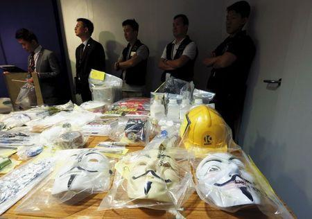 Police officers stand in front of Guy Fawkes masks seized along with explosives, during a news conference in Hong Kong, China June 15, 2015. REUTERS/Bobby Yip -