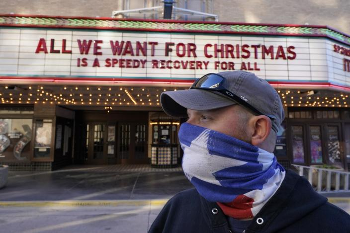 Employee Grayson Allred poses for a photo after putting up a message on the front marquee at the Paramount Theatre on Wednesday, Dec. 16, 2020, in Abilene, Texas. The theatre has closed down operations indefinitely due to rising cases of COVID-19 in the city. (AP Photo/Tony Gutierrez)
