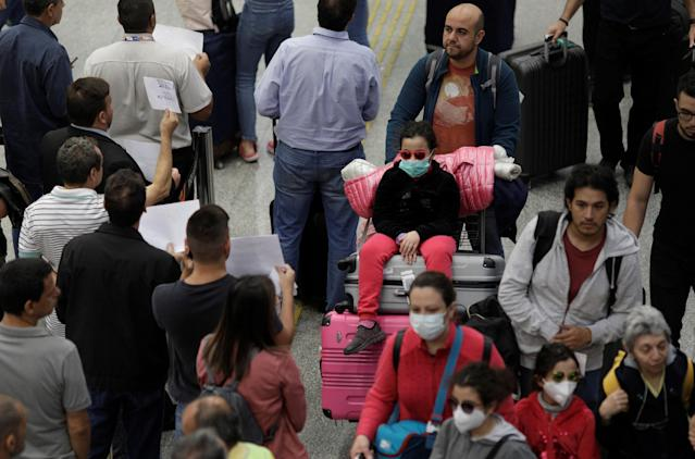 Travellers wear protective face masks at Galeao International Airport in Rio de Janeiro, Brazil, after reports of the coronavirus March 6, 2020. REUTERS/Ricardo Moraes