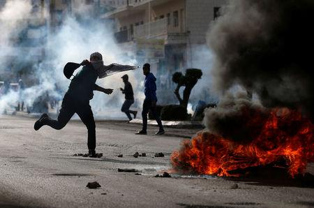Palestinian demonstrator hurls stones towards Israeli troops during clashes at a protest near the Jewish settlement of Beit El, near the West Bank city of Ramallah