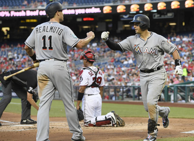 Miami Marlins' Martin Prado, right, celebrates his three-run home run with J.T. Realmuto (11) during the second inning of a baseball game against the Washington Nationals, Thursday, July 5, 2018, in Washington. At rear is Nationals catcher Pedro Severino. (AP Photo/Nick Wass)