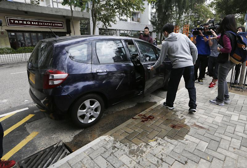 "A police officer, center, tries to remove the car of Kevin Lau, the former Ming Pao chief editor, after he was attacked in a street in Hong Kong, China Wednesday, Feb. 26, 2014. The former editor of the Hong Kong newspaper whose abrupt dismissal in January sparked protests over press freedom has been stabbed, police said on Wednesday. Police said a man wearing a motorcycle helmet ""suddenly"" attacked Kevin Lau on Wednesday morning with a knife and then fled on a motorcycle driven by another man. (AP Photo/Kin Cheung)"