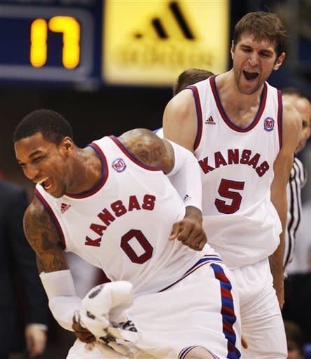 Kansas forward Thomas Robinson (0) and center Jeff Withey (5) celebrate as a time out is called during the first half of an NCAA college basketball game against Oklahoma State in Lawrence, Kan., Saturday, Feb. 11, 2012. (AP Photo/Orlin Wagner)