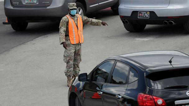 PHOTO: A National Guardsman directs traffic at a drive-thru COVID-19 testing site outside Hard Rock Stadium in Miami Gardens, Florida, on July 8, 2020. Florida has become one of the nation's hot spots for the novel coronavirus. (Wilfredo Lee/AP)