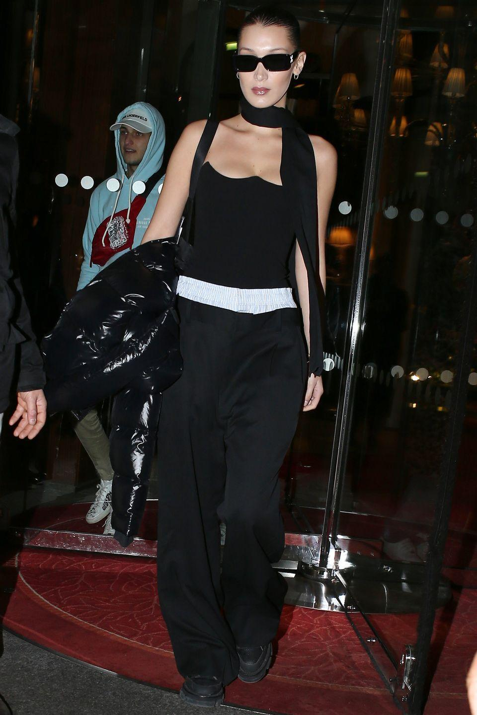 <p>Leaving her hotel in Paris in a strapless Versace bustier top, black slouchy wide-legged pants, a skinny scarf, and sunglasses.</p>