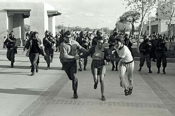 Black-and-white image of three running young people, chased by a dozen armed soldiers