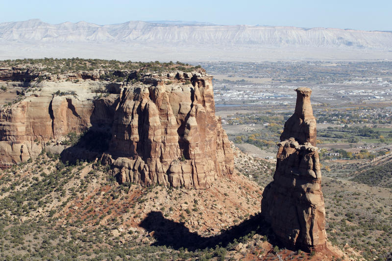 In this photograph taken on Saturday, Oct. 30, 2010, Independence Monument stands out against the backdrop of the Book Cliffs at the Colorado National Monument south of Fruita, Colo. Colorado National Monument is 32 square miles of red rock monoliths and canyons just south of Interstate 70 on the border of Colorado and Utah.   (AP Photo/Judith Kohler)