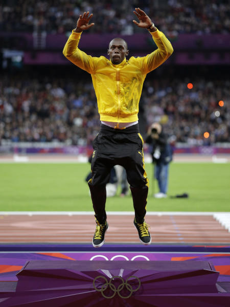 Jamaica's Usain Bolt leaps onto the podium to receive his gold medal for the men's 100-meters during the athletics in the Olympic Stadium at the 2012 Summer Olympics, London, Monday, Aug. 6, 2012. (AP Photo/Matt Slocum)