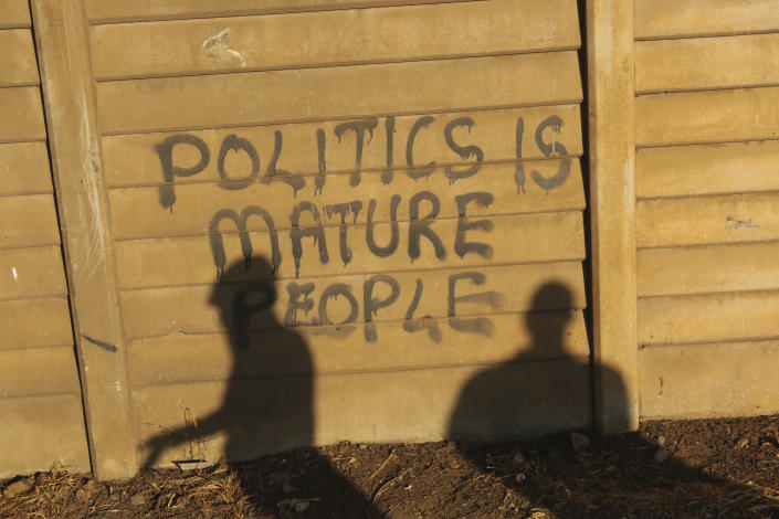 "People stand near a wall with a poltical graffiti message in this Monday, Aug, 17, 2020 photo. Unable to protest on the streets, some in Zimbabwe are calling themselves ""keyboard warriors"" as they take to graffiti and social media to pressure a government that promised reform but is now accused of gross human rights abuses.(AP Photo/Tsvangirayi Mukwazhi)"