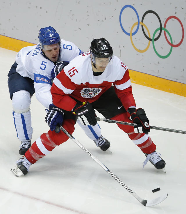 Finland defenseman Lasse Kukkonen reaches for he puck against Austria forward Manuel Latusa in the second period of a men's ice hockey game at the 2014 Winter Olympics, Thursday, Feb. 13, 2014, in Sochi, Russia. (AP Photo/Mark Humphrey)