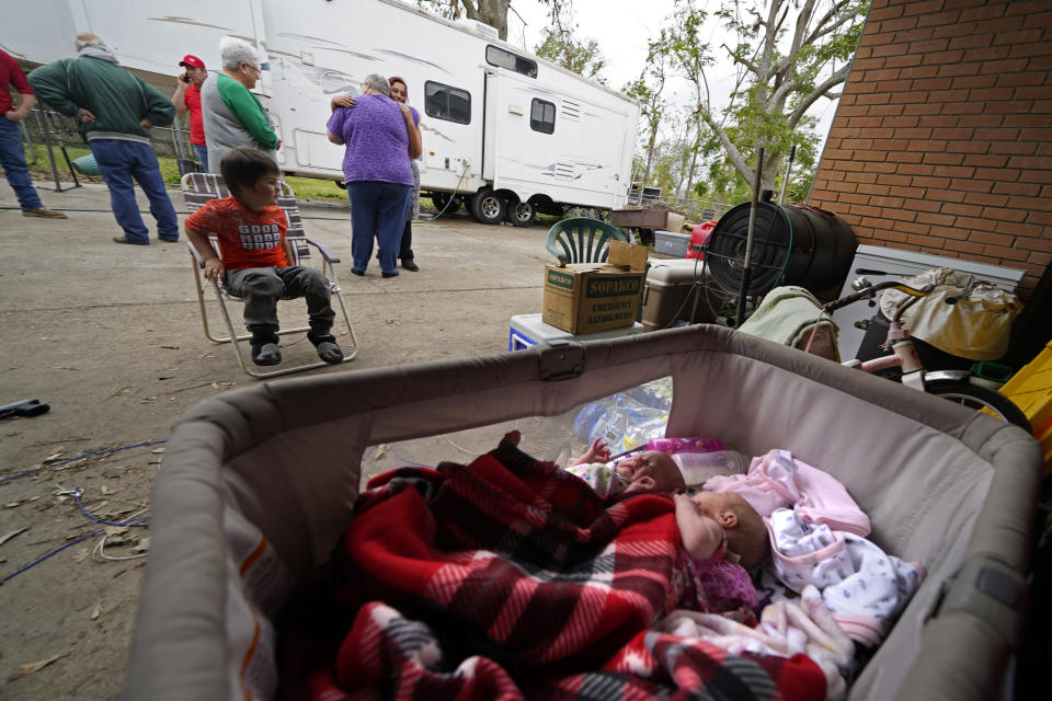 Two-week old twins Lilly and Zoey lay in a bassinet as Hannah Bourque hugs church volunteers who brought Christmas presents to her son Conner, seated, outside the camper she is living in with her grandfather, while her mother lives in a tent in the backyard of their heavily damaged home, in the aftermath of Hurricane Laura and Hurricane Delta, in Lake Charles, La., Friday, Dec. 4, 2020. (AP Photo/Gerald Herbert)